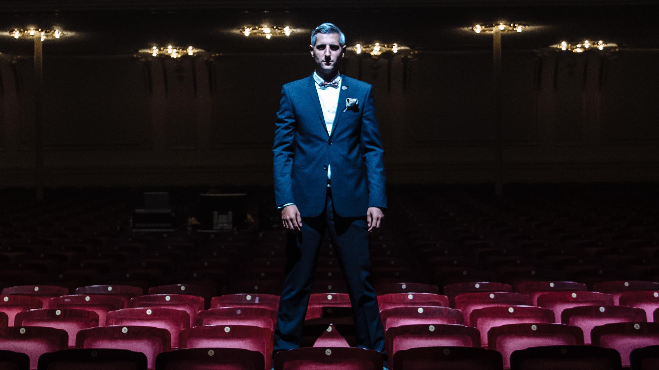 Michel Abdollahi steht auf den Stühlen eines abgedunkelten Theatersaals
