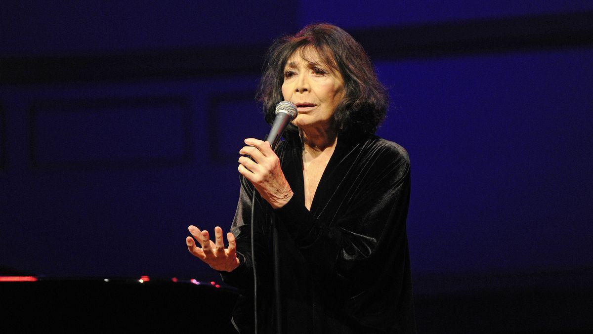 Juliette Gréco mit halblangem Haar in schwarz gekleidet singend mit einem Mikrofon in der Hand