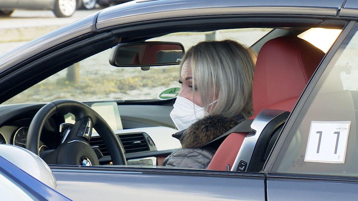 Eine Single-Frau sitzt mit Maske in ihrem Auto und datet