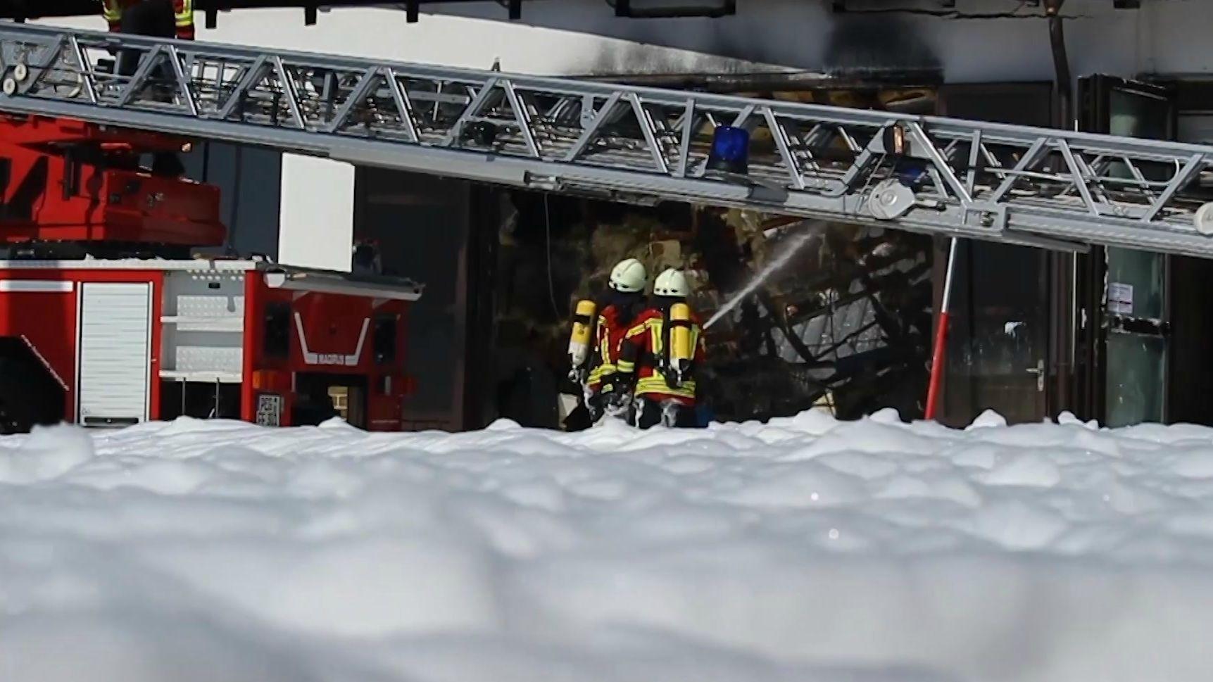 Zwei Feuerwehrmänner beim Löschen eines Brandes