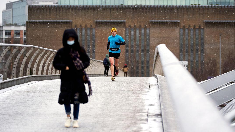 Ein Läufer überquert bei Schneefall die Millennium Bridge in London.