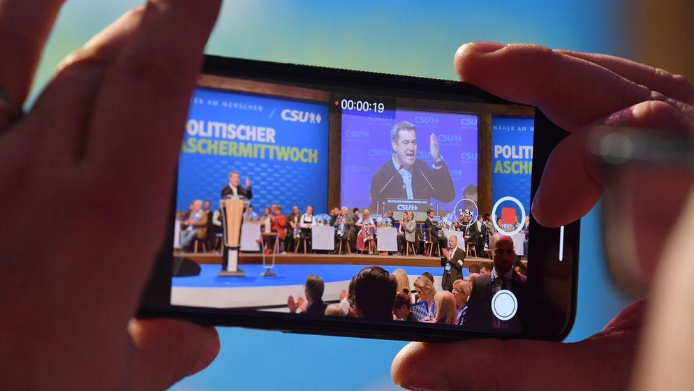 Markus Söder, CSU-Vorsitzender und Ministerpräsident aus Bayern, spricht beim Politischen Aschermittwoch der CSU - gefilmt von einem Smartphone. | Bild:pa/dpa/Peter Kneffel