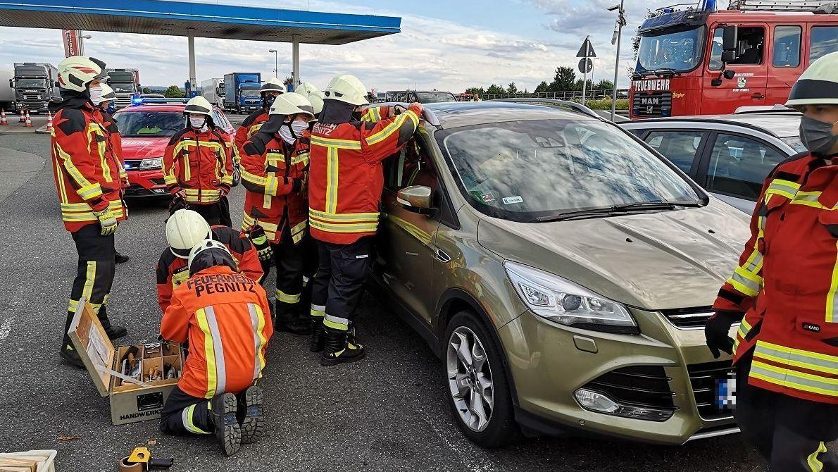 Feuerwehrleute öffnen die Scheibe eines Autos.