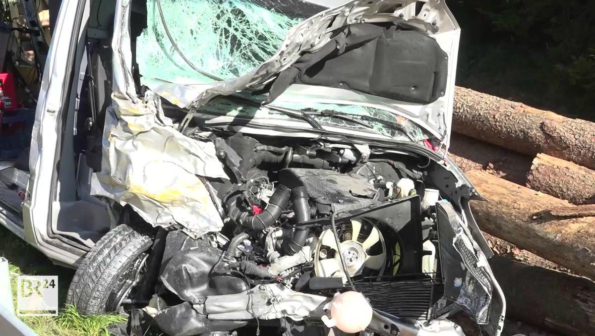 Unter einer aufgerissenen Motorhaube eines Autos befindet sich der zerstörte Motor, darunter ist ein Reifen zu sehen.