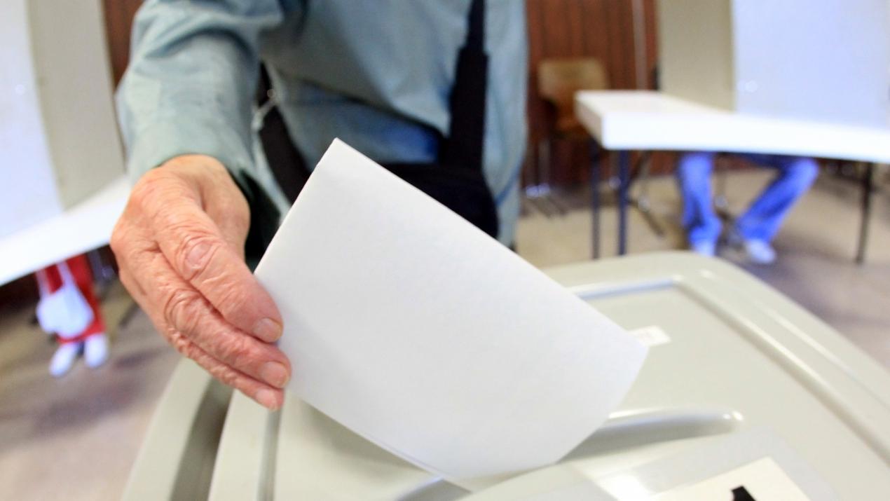 Symbolbild: Ein Stimmzettel wird in eine Wahlurne geworfen.