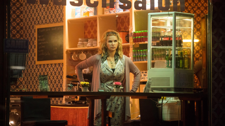 """Veronica Ferres steht in einem Schaufenster mit der Aufschrift """"Waschsalon"""", neben ihr sind ein deckenhohes Regal und ein Getränkeautomat"""
