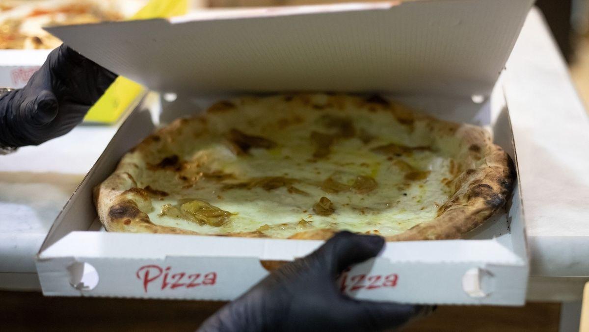 Eine Pizza wird in einen Karton gepackt