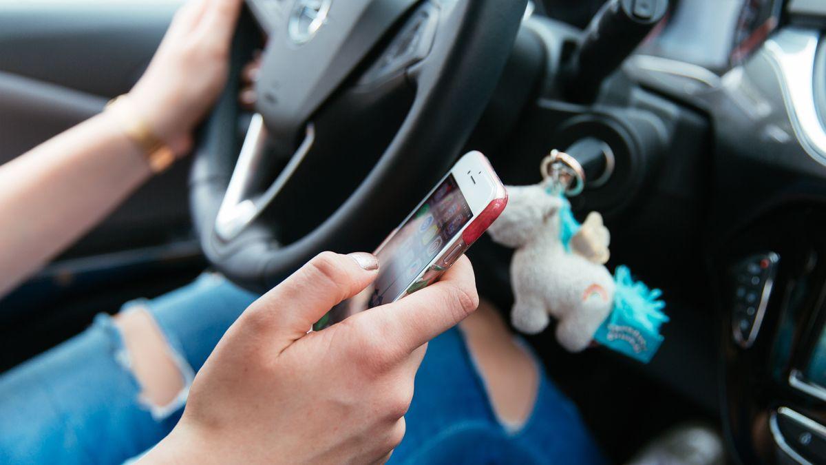 Eine junge Frau benutzt ihr Smartphone während des Fahrens
