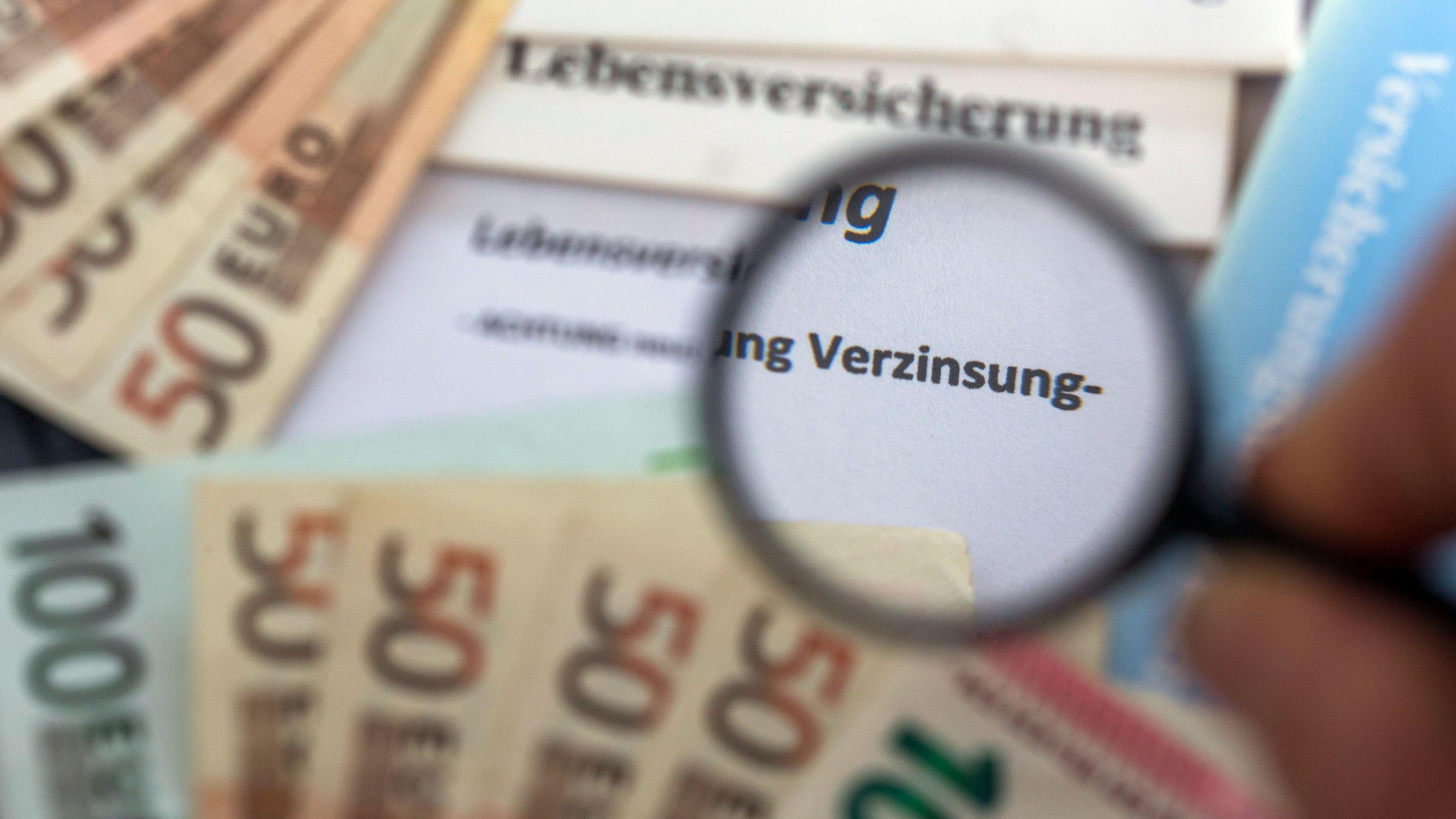 """Illustration zum Thema Lebensversicherung mit Geldscheinen und einer Lupe, durch die das Wort """"Verzinsung"""" zu sehen ist."""