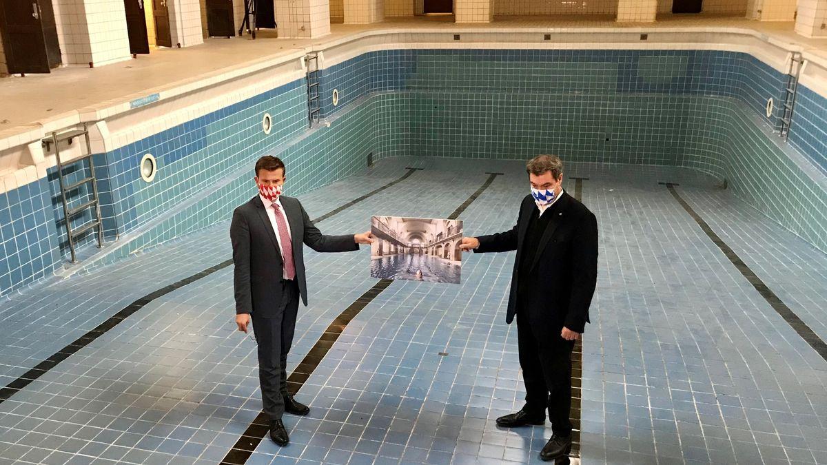Nürnbergs Oberbürgermeister Marcus König und Bayerns Ministerpräsident Markus Söder im leeren Schwimmbecken des Volksbads mit einem alten Bild der Jugendstilperle.