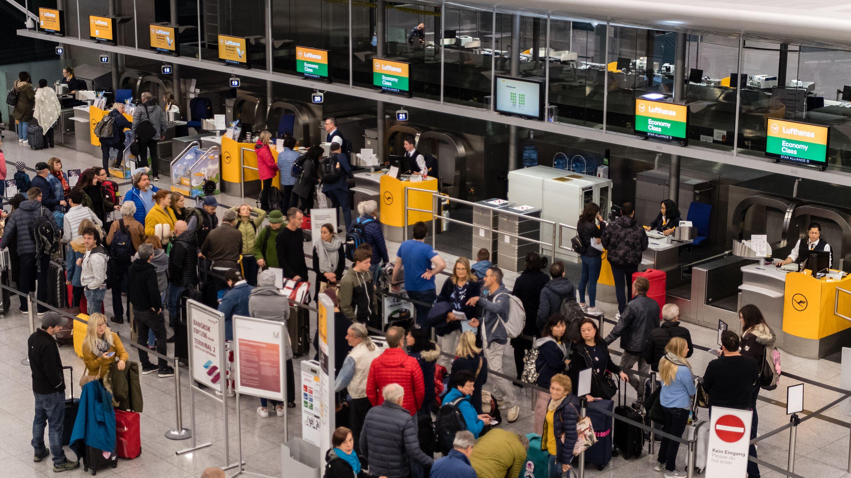 Passagierschlangen vor Schaltern auf Flughafen