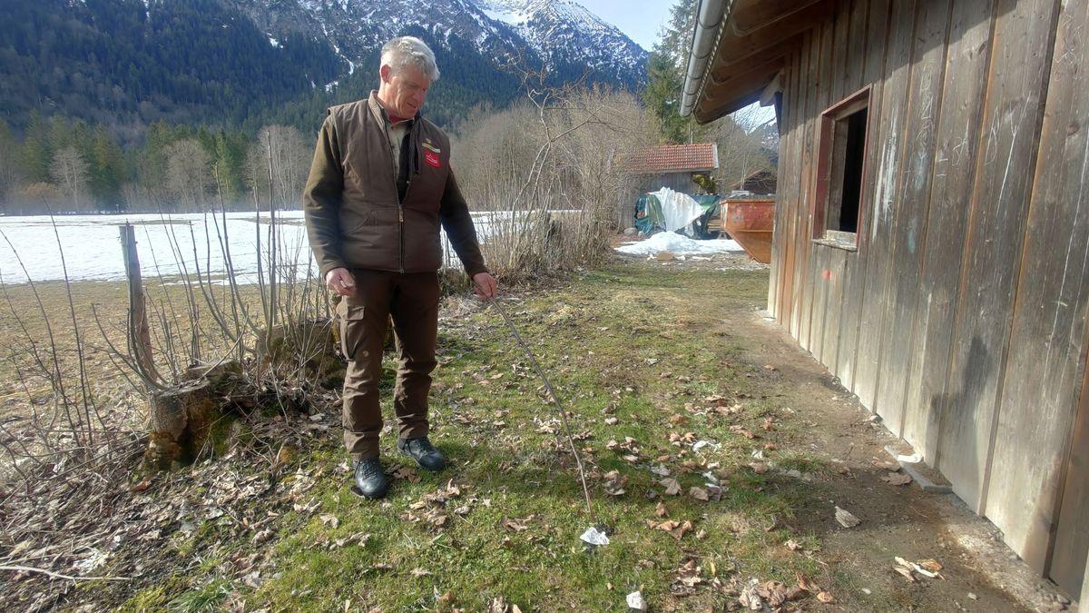 Ranger Thomas Weber hinter dem Stadel in Graswang zwischen menschlichen Hinterlassenschaften.