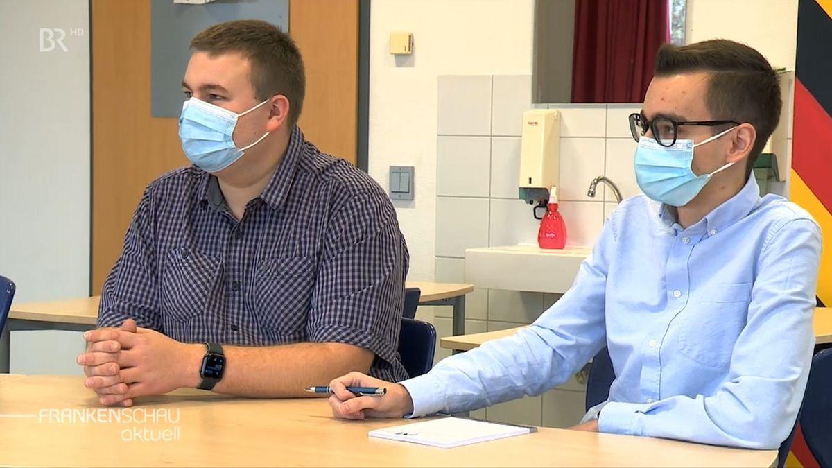 Zwei Personen sitzen an einem Tisch und tragen eine Mund-Nasen-Bedeckung.