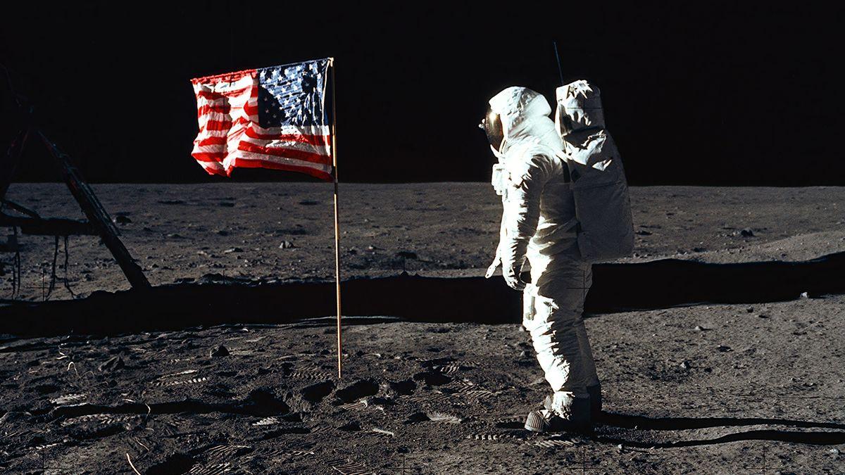 """""""Buzz"""" Aldrin steht im Raumanzug neben der US-Flagge auf dem Mond."""