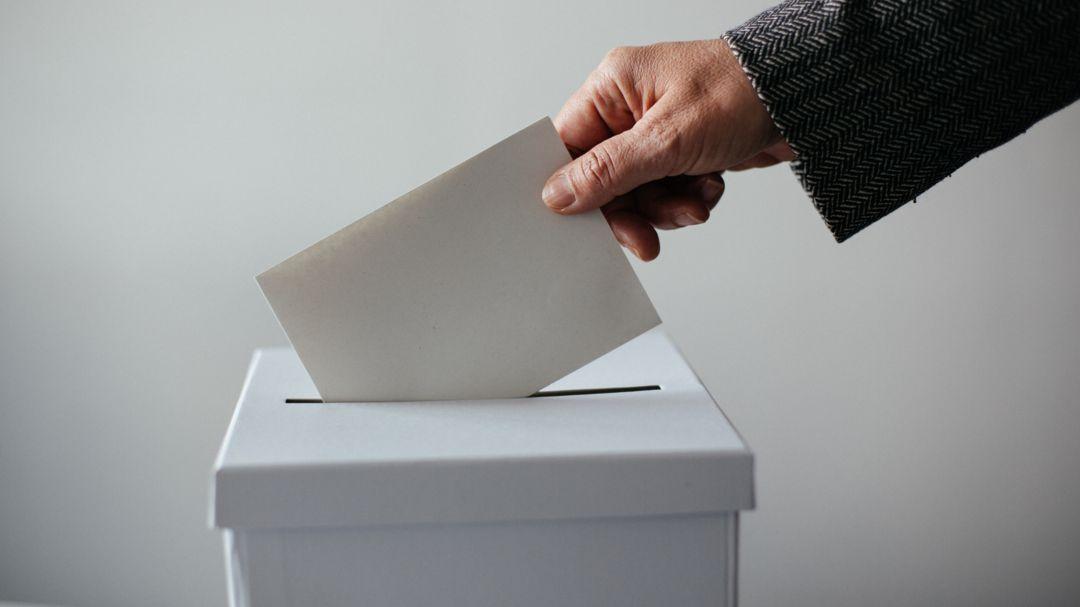 Jemand wirft einen Wahlschein in eine Wahlurne.