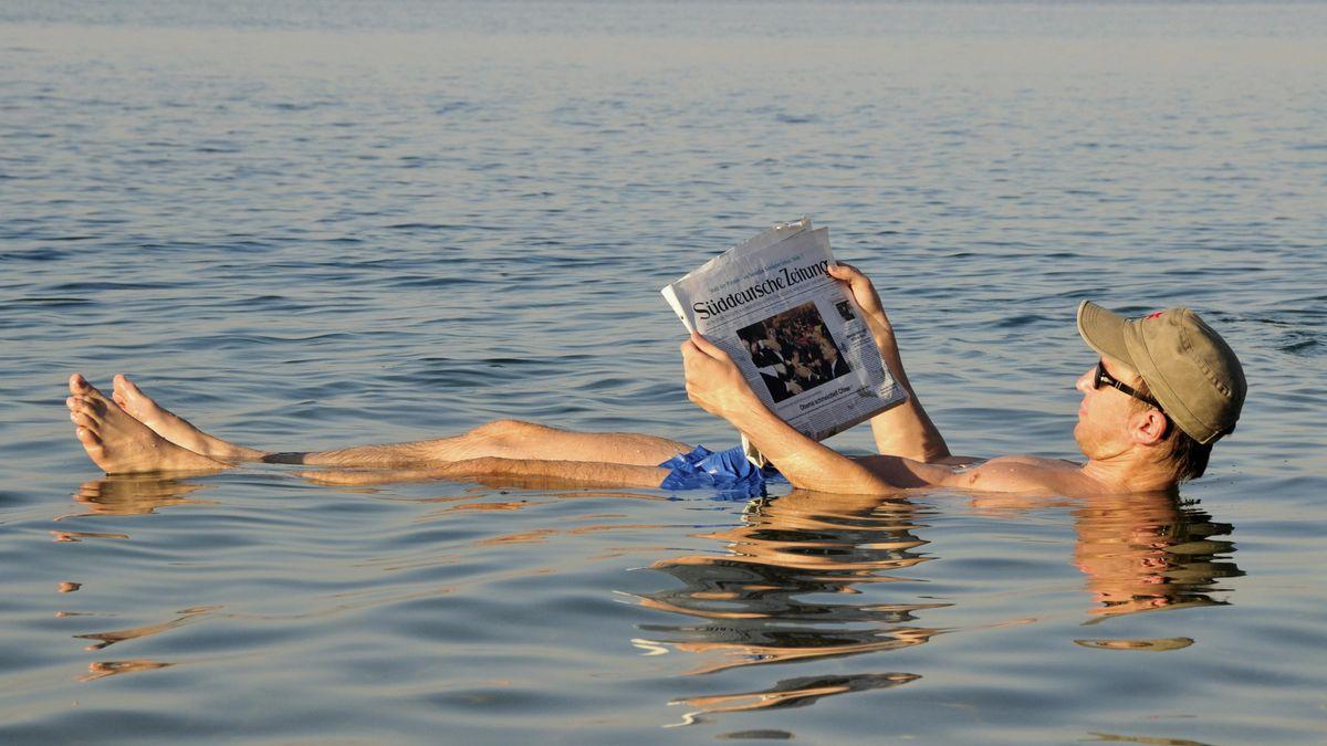 Schwimmer hält Zeitung in die Luft