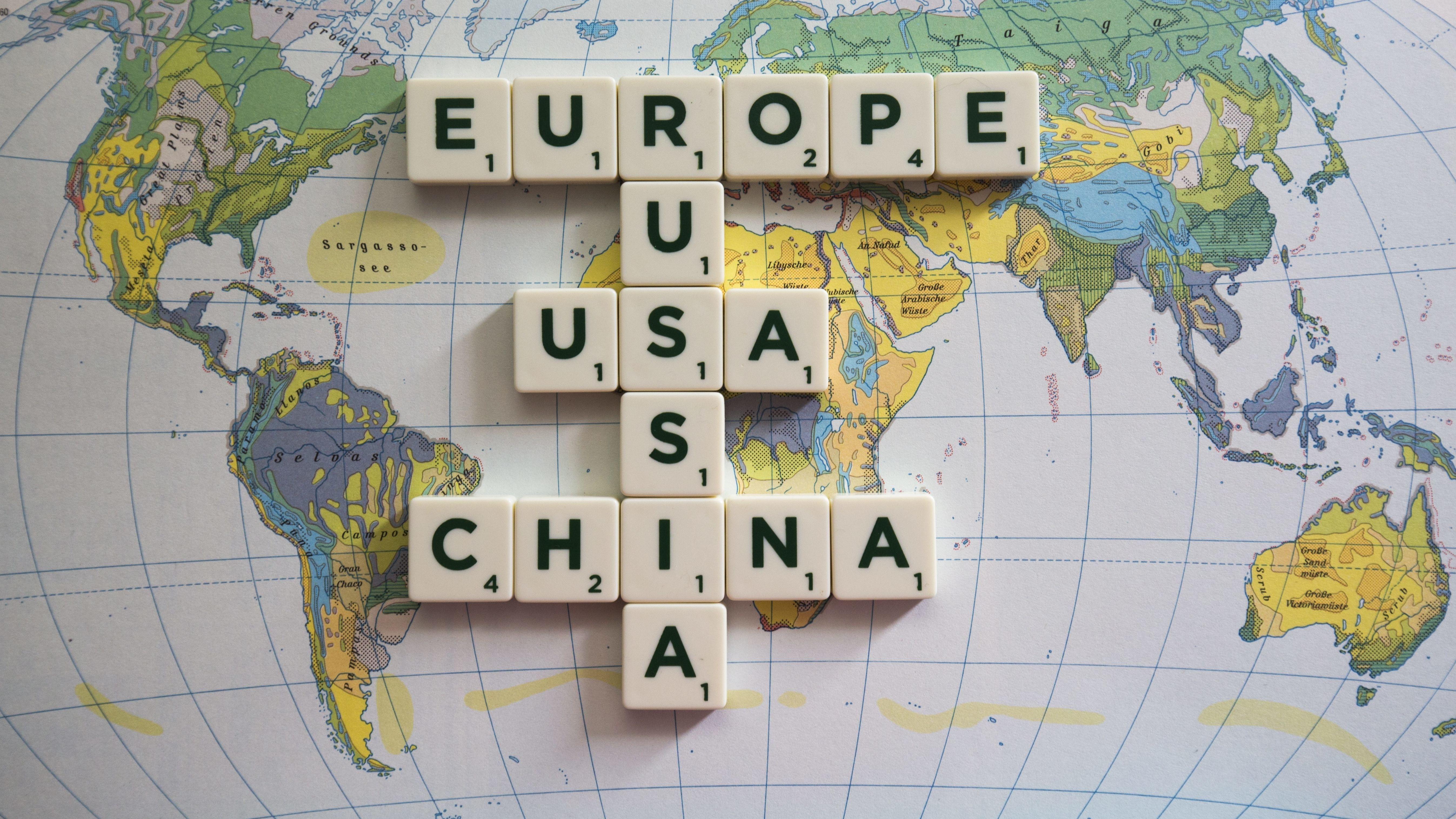 Scrabble-Steine liegen auf einer Weltkarte (Symbolbild Weltpolitik)