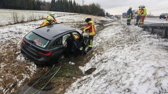 Ein Auto steht im Straßengraben neben der Autobahn, davor Feuerwehrleute.