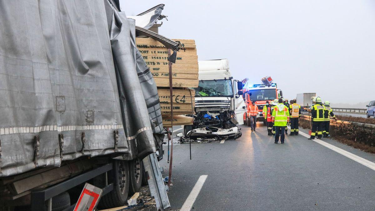 Einsatzkräfte der Feuerwehr stehen neben zwei verbeulten Lastwagen.