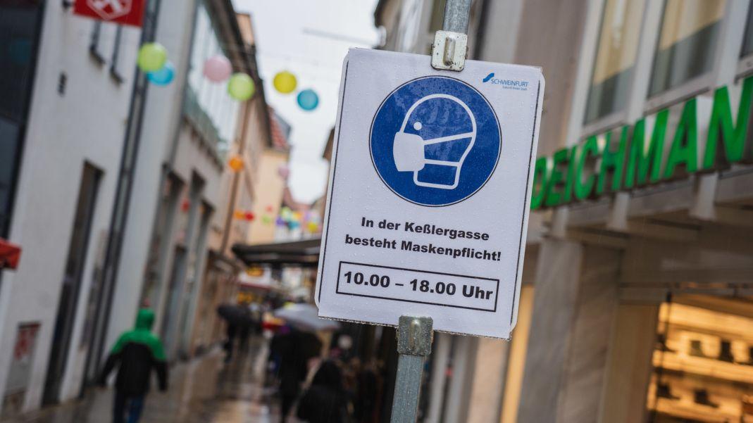 In einer schmalen Gasse in der Schweinfurter Innenstadt ist ein Schild aufgestellt, das auf die Maskenpflicht hinweist.