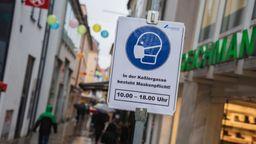 In einer schmalen Gasse in der Schweinfurter Innenstadt ist ein Schild aufgestellt, das auf die Maskenpflicht hinweist.   Bild:dpa-Bildfunk/Nicolas Armer