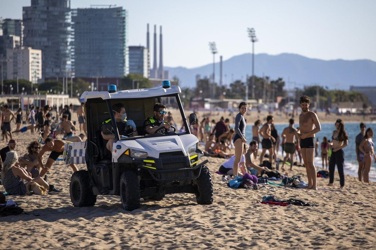 27.05.2020, Spanien, Barcelona: Polizeibeamte patrouillieren am Strand von Barcelona. Mit mehr als 235 000 Infektionsfällen und über 27 000 Toten ist Spanien eines der von der Pandemie am schwersten betroffenen Länder der Welt. Foto: Emilio Morenatti/AP/dpa +++ dpa-Bildfunk +++