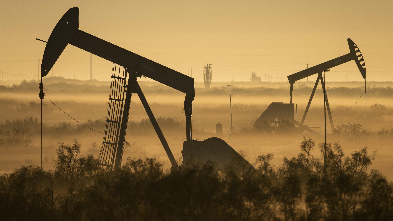 Nebelbänke umhüllen Ölpumpen in einem Tal in Texas.