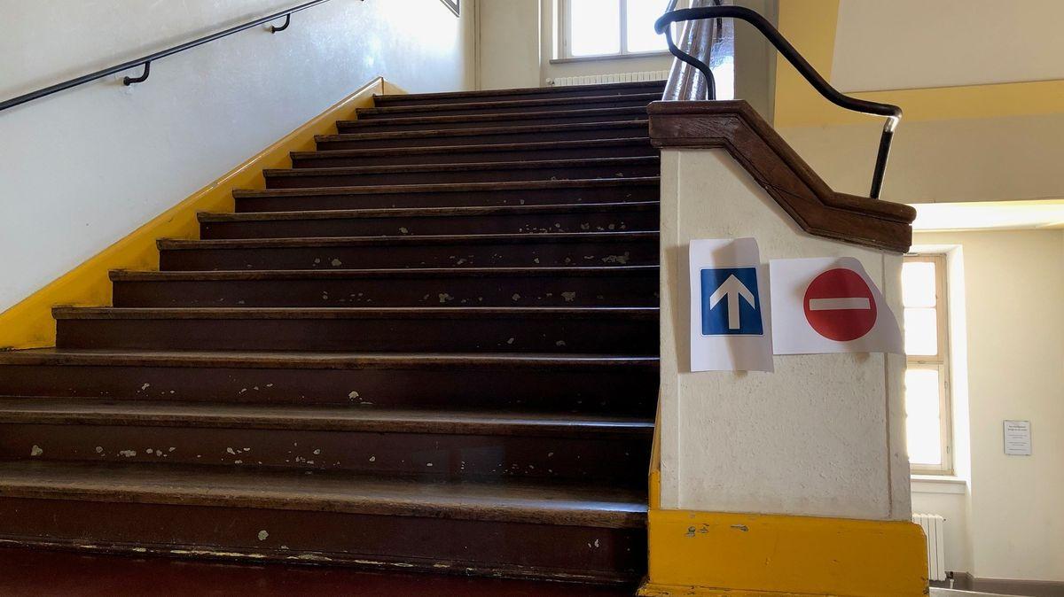 Ein Treppenhaus in einer Schule, dazu zwei Schilder, dass hier Einbahnstraße ist.