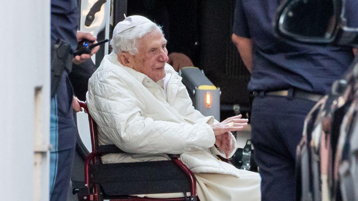 Der emeritierte Papst Benedikt XVI wird mit einem Rollstuhl in einen Bus geschoben.