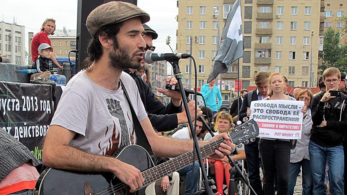 Ein Mann mit Schiebermütze und Gitarre singt bei einer Demonstration in ein Mikrofon.