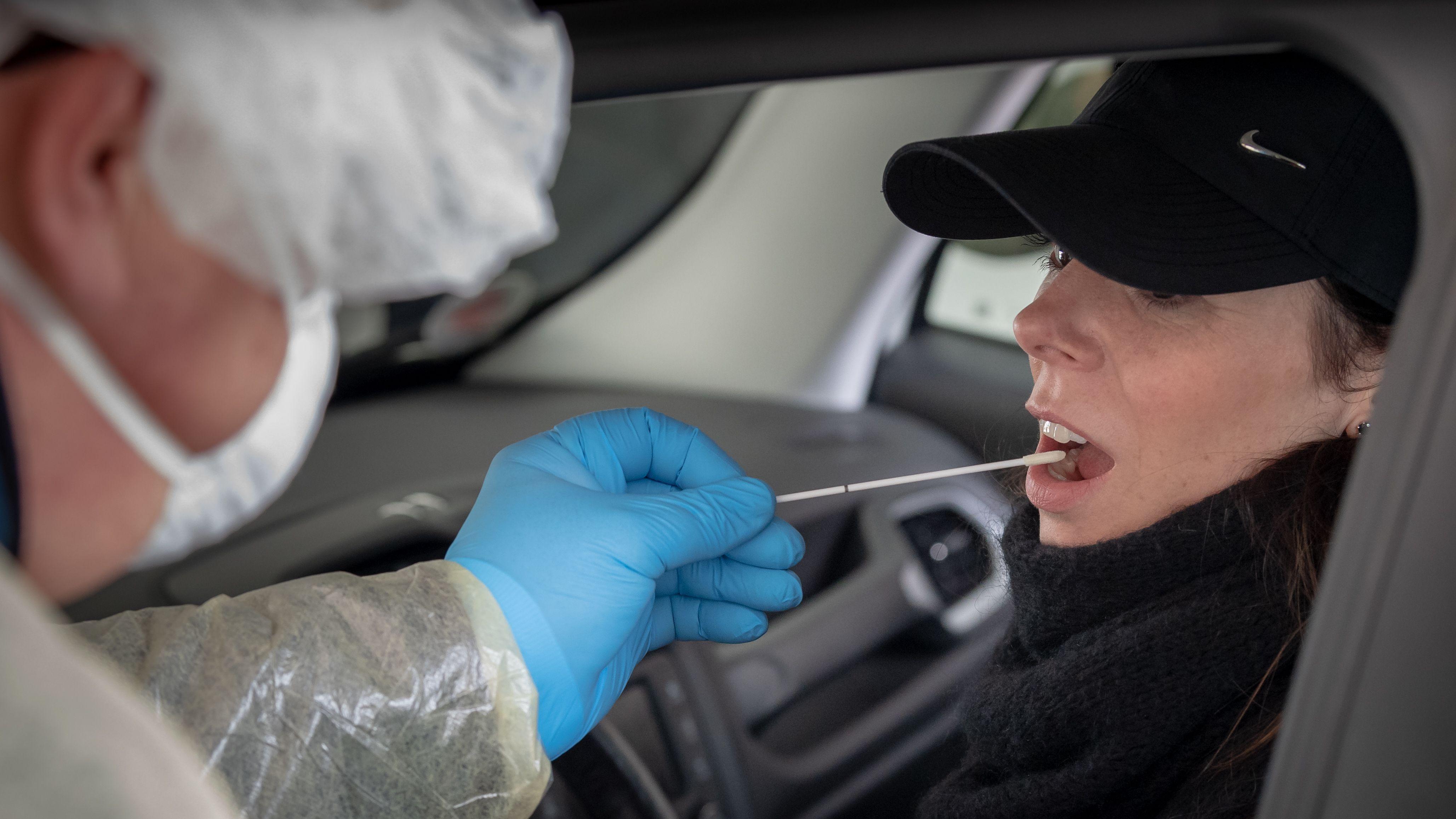 Ein Arzt nimmt einen Testabstrich bei einer Patientin im Auto.