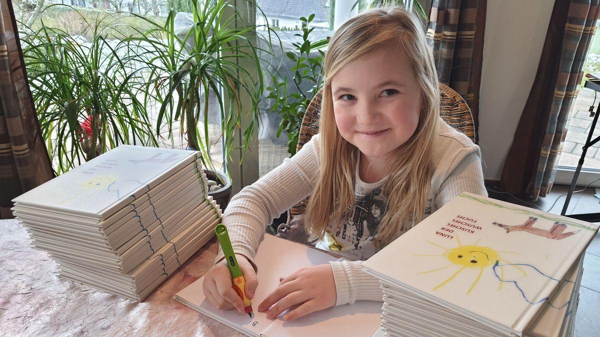 Jana Küffner sitzt zwischen zwei Stapeln ihres Buches. Sie nummieriert und signiert jedes Einzelne.