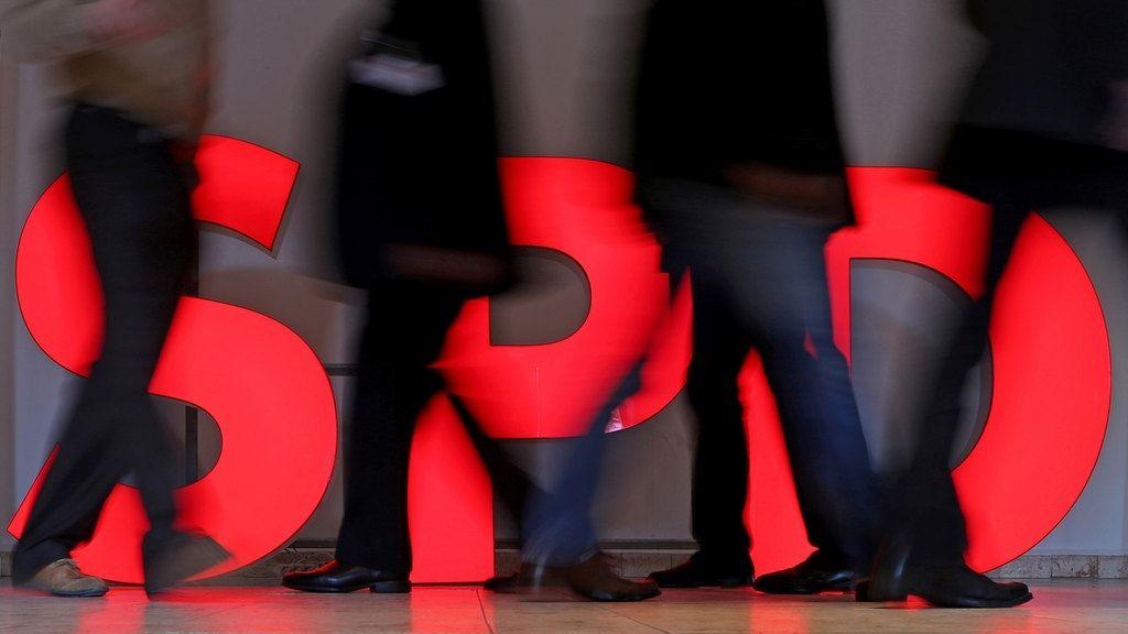 Menschen laufen vor SPD-Logo