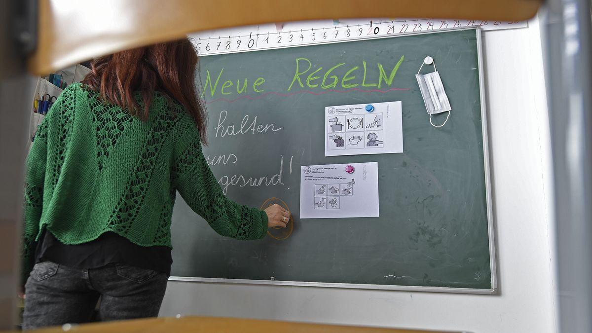 Lehrerin schreibt Corona-Regeln an die Tafel