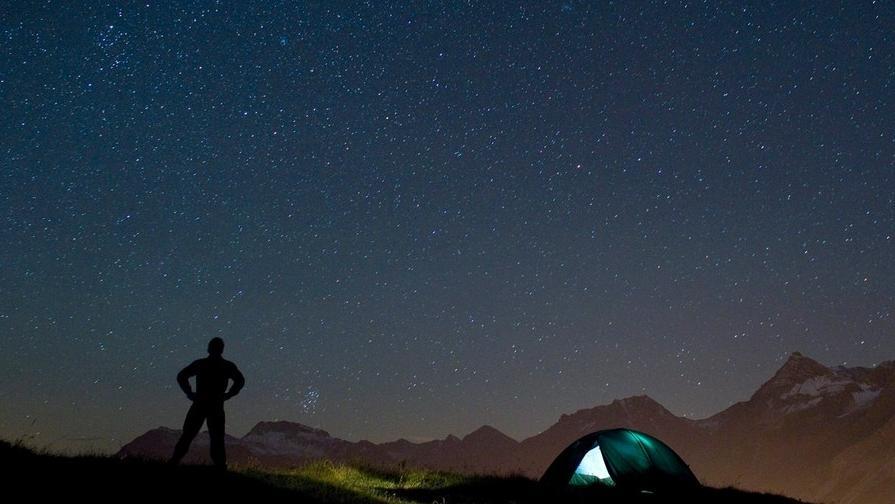 Ein Beobachter steht in der Sommernacht unter dem Sternenhimmel