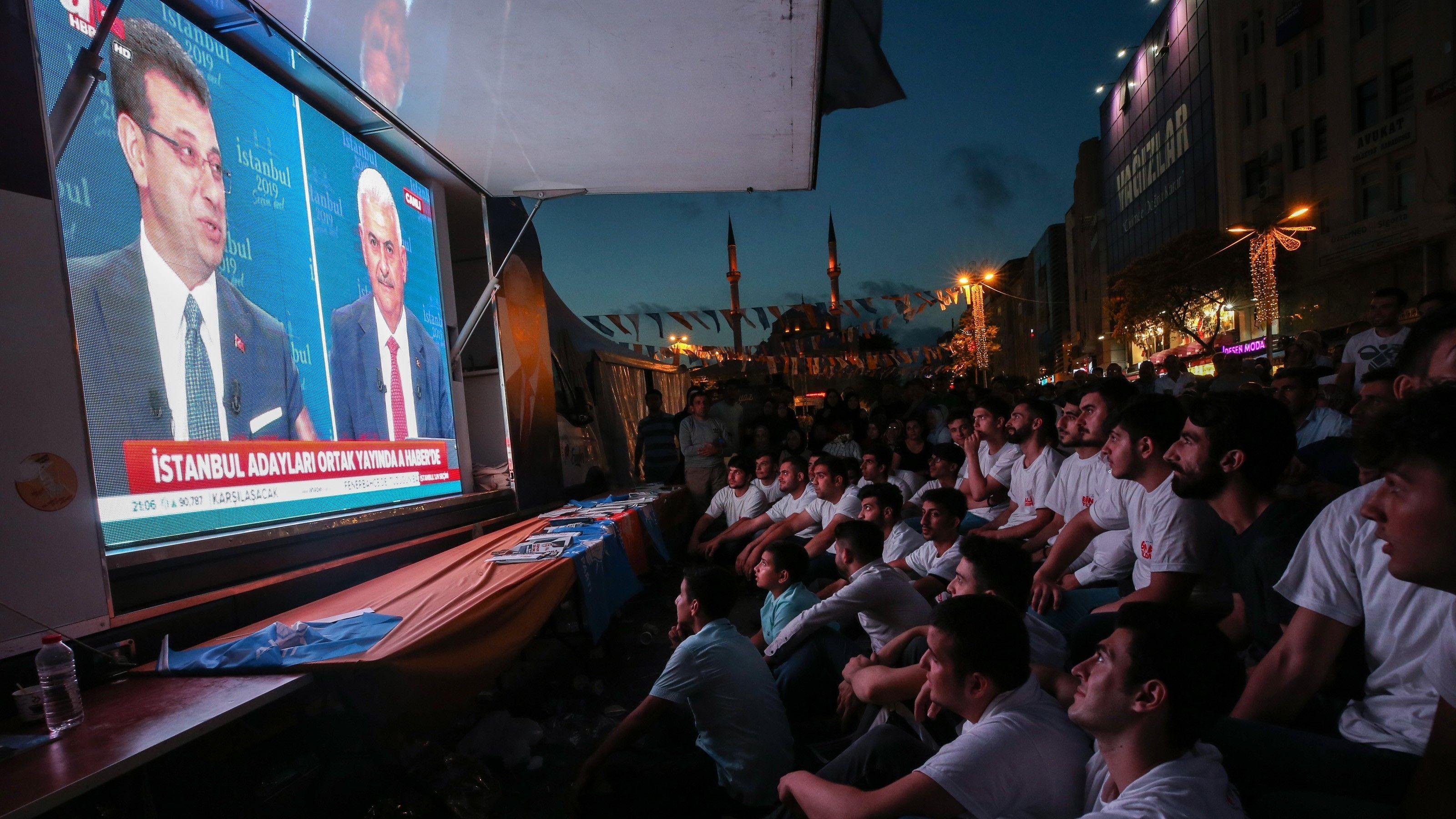 Menschen verfolgen TV-Duell zwischen Yildirim (AKP) und Imamoğlu (CHP) vor Bürgermeisterwahl in Istanbul unter freiem Himmel