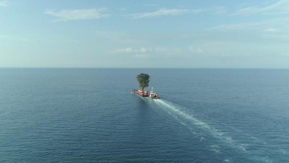 """Kleines Schiff landet in einem gigantischen blauen Meer auf einer winzige Insel: Szene aus """"Taming the Garden"""" von Salome Jashi"""