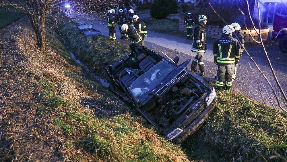 Das Bild zeigt einen stark beschädigten Wagen im Straßengraben, flankiert von Feuerwehrmännern.