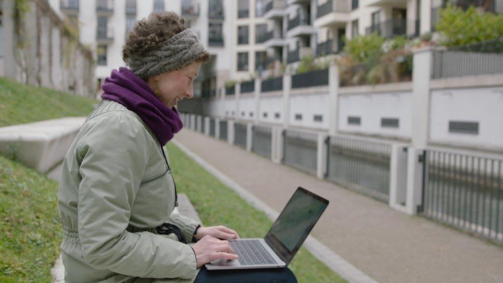 Lea sitzt mit dem Laptop im Freien
