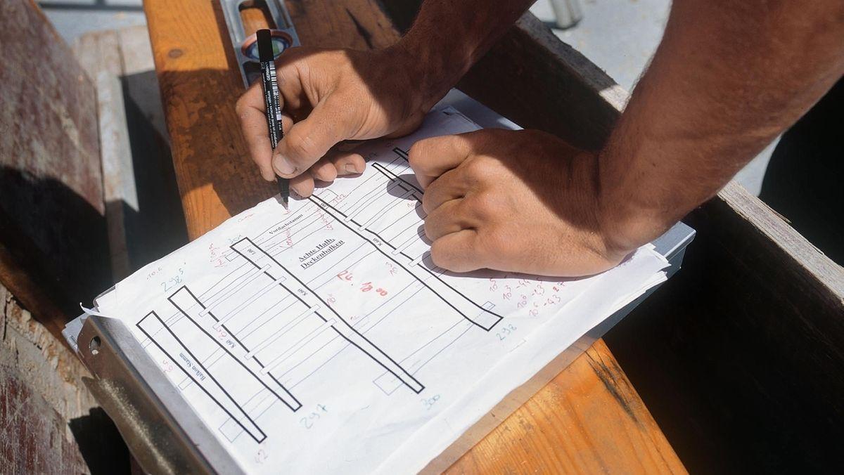 Handwerker mit Bauplan beim Bau eines Holzhauses