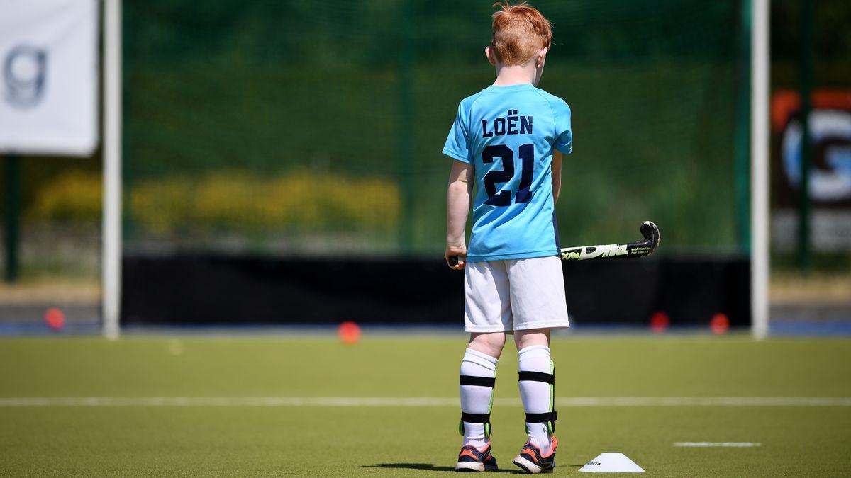 Ein Kind steht allein mit seinem Hockeyschläger vor einem Tor.