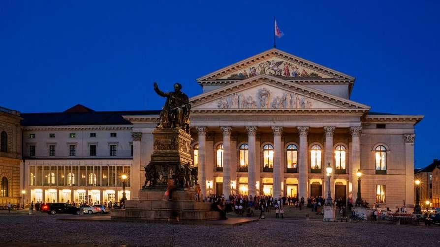Blick über den Max-Joseph-Platz mit dem Denkmal Maximilian I. Joseph in München auf das Residenz- und das Nationaltheater in den Abendstunden vor Beginn einer Aufführung.