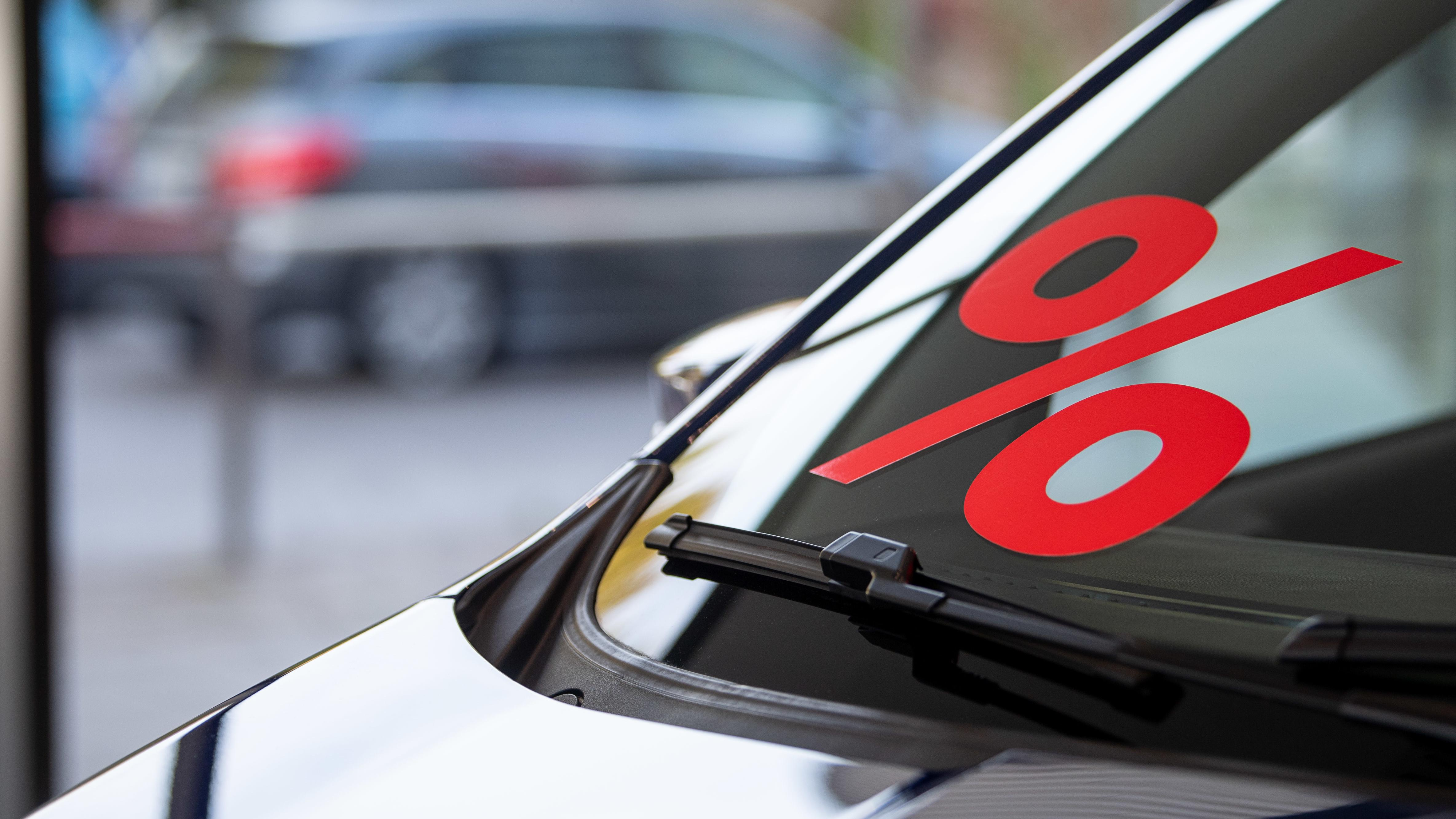Ein Prozentzeichen klebt auf der Scheibe eines Autos