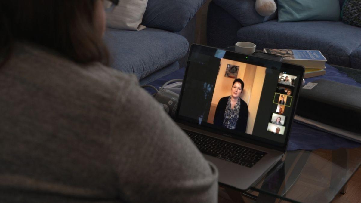 Eine Frau sitzt vor einem Laptop und tauscht sich dort mit anderen Menschen in einer Post-Covid-Selbsthilfegruppe aus.