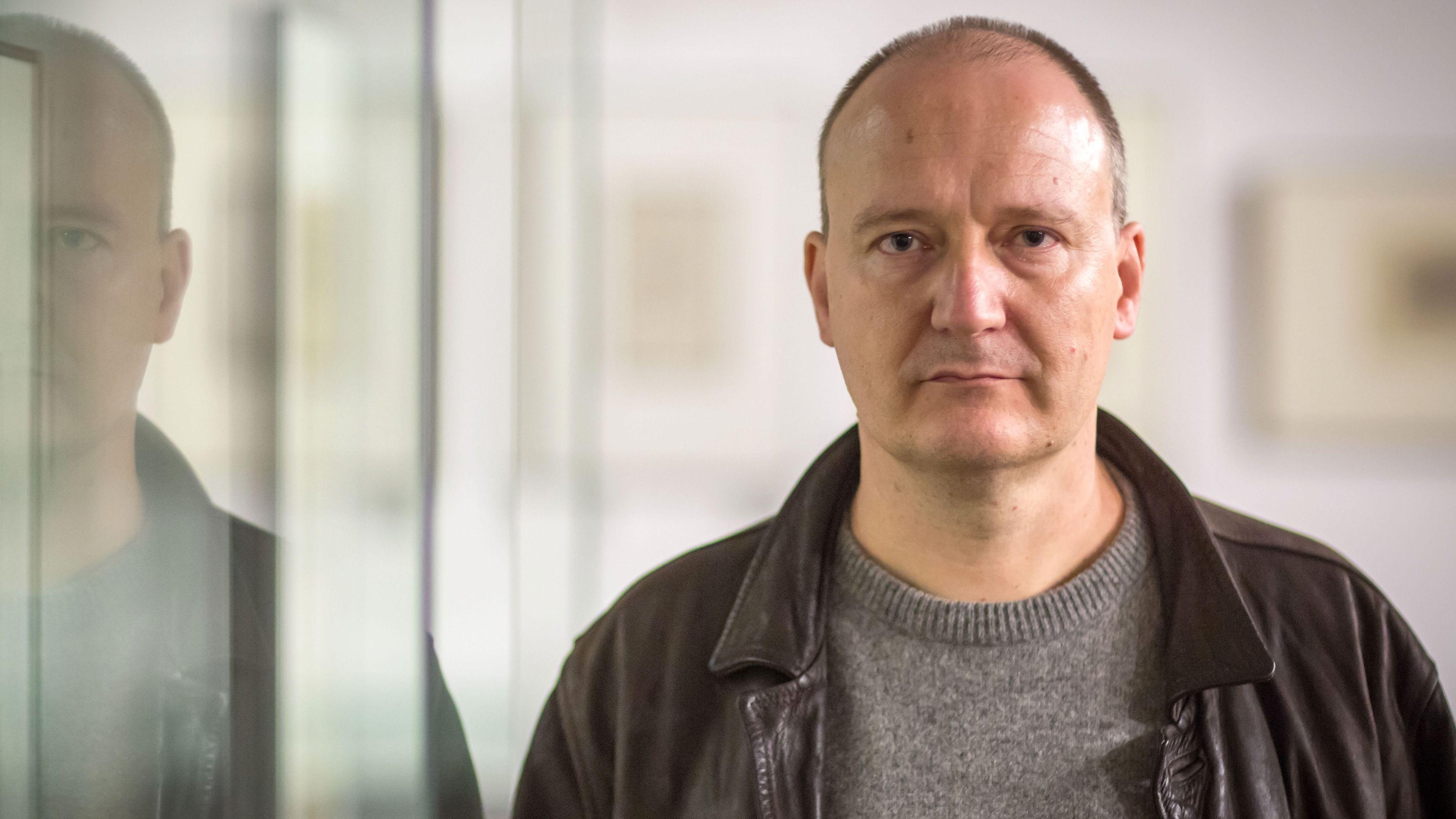 Autor Thomas Brussig blickt, neben einer Scheibe stehend, ernst in die Kamera