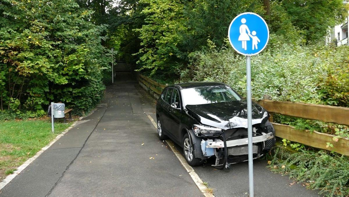 Ein verbeultes Auto ist auf einem Fußgängerweg gegen einen Holzzaun gekracht.