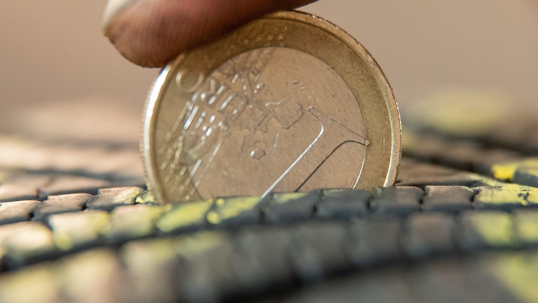 Eine 1 Euro-Münze steckt im Reifenprofil