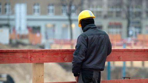 Ein Bauarbeiter mit Helm auf einer Baustelle.