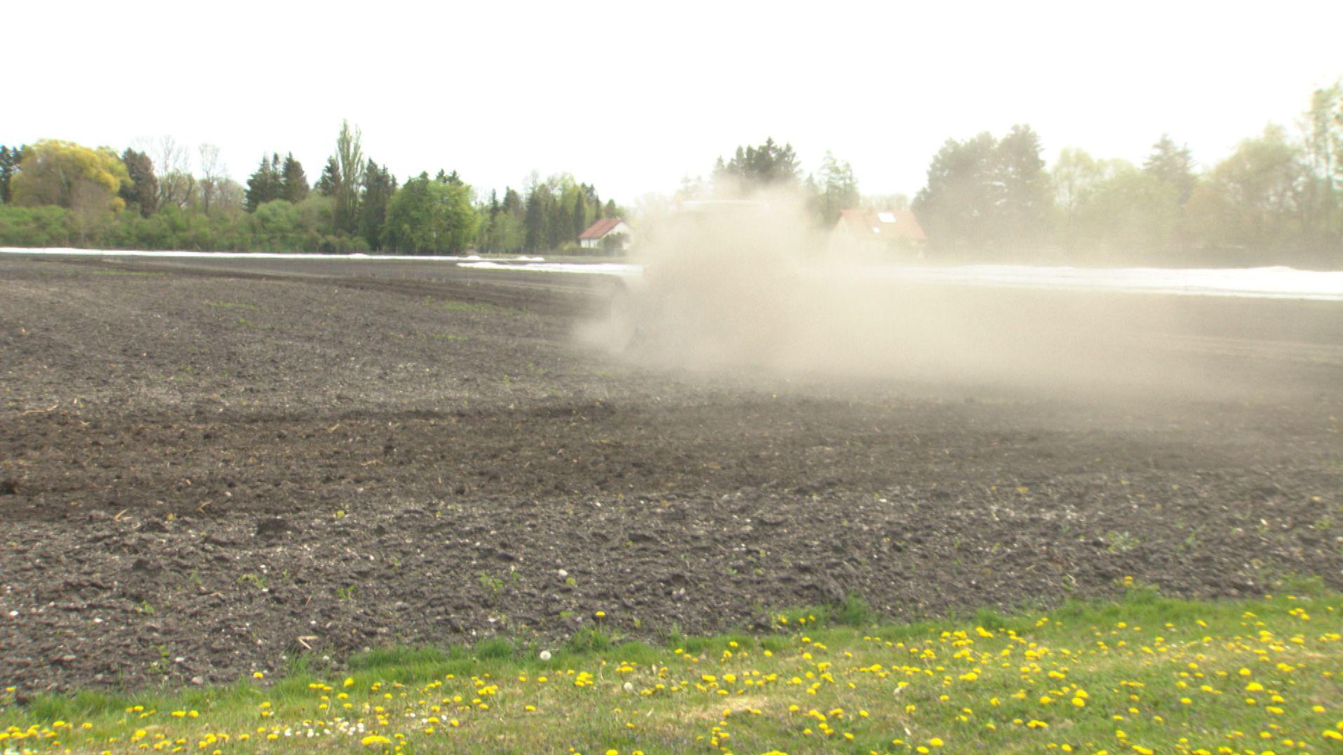 Eine Staubwolke hinter einem Traktor auf trockenem Acker.