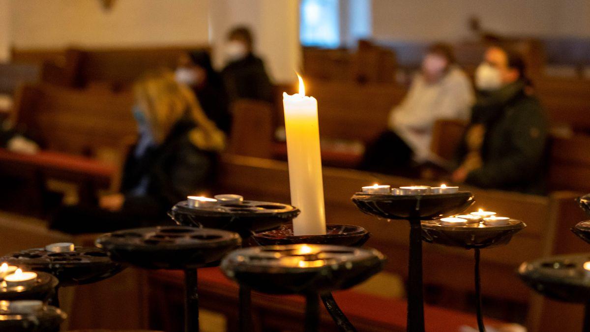 Gäste des ökumenischen Gedenkgottesdienstes für die Opfer und Leidtragenden der Corona-Pandemie sitzen in der St. Nikolai Kirche in Kiel in den Bänken.